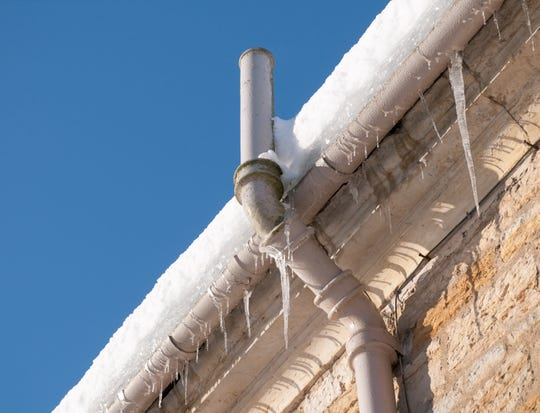 Icicles hanging from the gutter, and snow on the roof causing drainage problems for an old building in winter.
