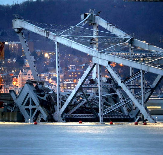 The demolished Tappan Zee Bridge, supported by chains, rests above the waterline  of the Hudson River.