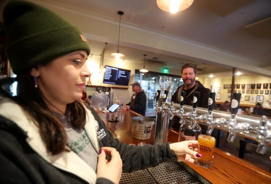 Crystal Borrega pours a beer for Bill Kanzler of Northport, Long Island, at the Captain Lawrence Brewery tasting room in Elmsford Jan. 17, 2019. New Rochelle is considering allowing brewery tasting rooms in the city without the means of production being in the same place.