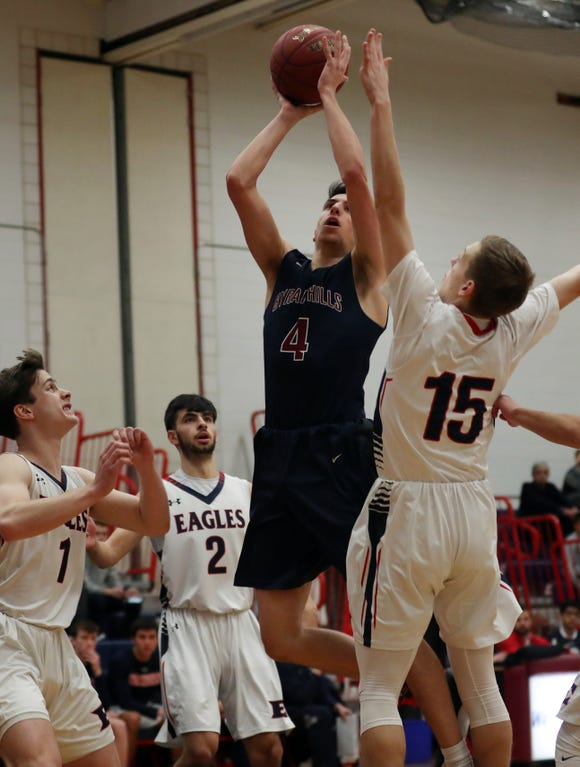 Byram Hills'  Mike Caporale (4) puts up a shot while surrounded by Eastchester defenders during boys basketball action at Eastchester High School Jan. 16, 2019. Byram Hills won the game 69-51.