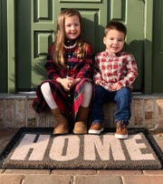 Kiley (left) and Kamden Farina on the steps of their new home.
