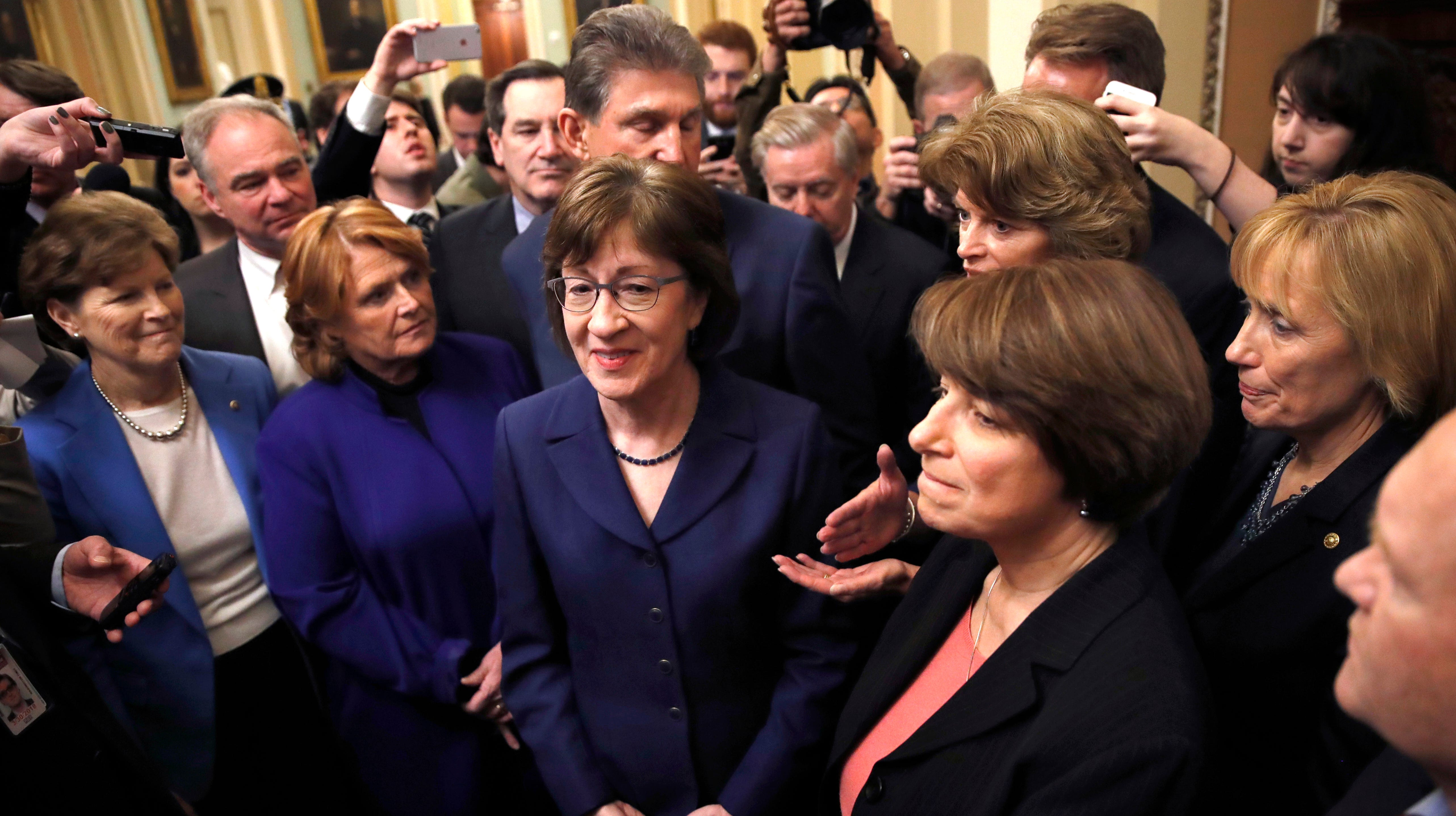 Sen. Susan Collins, R-Maine, center, and a bipartisan group of senators are pictured at the Capitol in Washington, Monday, Jan. 22, 2018. From left are, Sen. Jeanne Shaheen, D-N.H., former Sen. Heidi Heitkamp, D-N.D., Collins, behind Collins is Sen. Joe Manchin, D-W.Va., Sen. Lisa Murkowski, R-Alaska, Sen. Amy Klobuchar, D-Minn., and Sen. Maggie Hassan, D-N.H.
