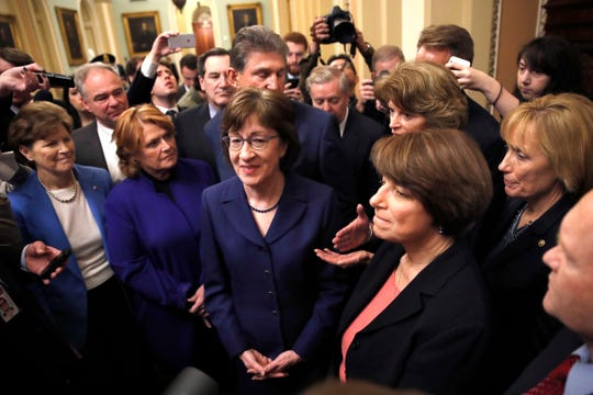 Sen. Susan Collins, R-Maine, center, and a bipartisan group of senators are pictured at the Capitol in Washington, Monday, Jan. 22, 2018. From left are, Sen. Jeanne Shaheen, D-N.H., former Sen. Heidi Heitkamp, D-N.D., Collins, behind Collins is Sen. Joe Manchin, D-W.Va., Sen. Lisa Murkowski, R-Alaska, Sen. Amy Klobuchar, D-Minn., and Sen. Maggie Hassan, D-N.H.