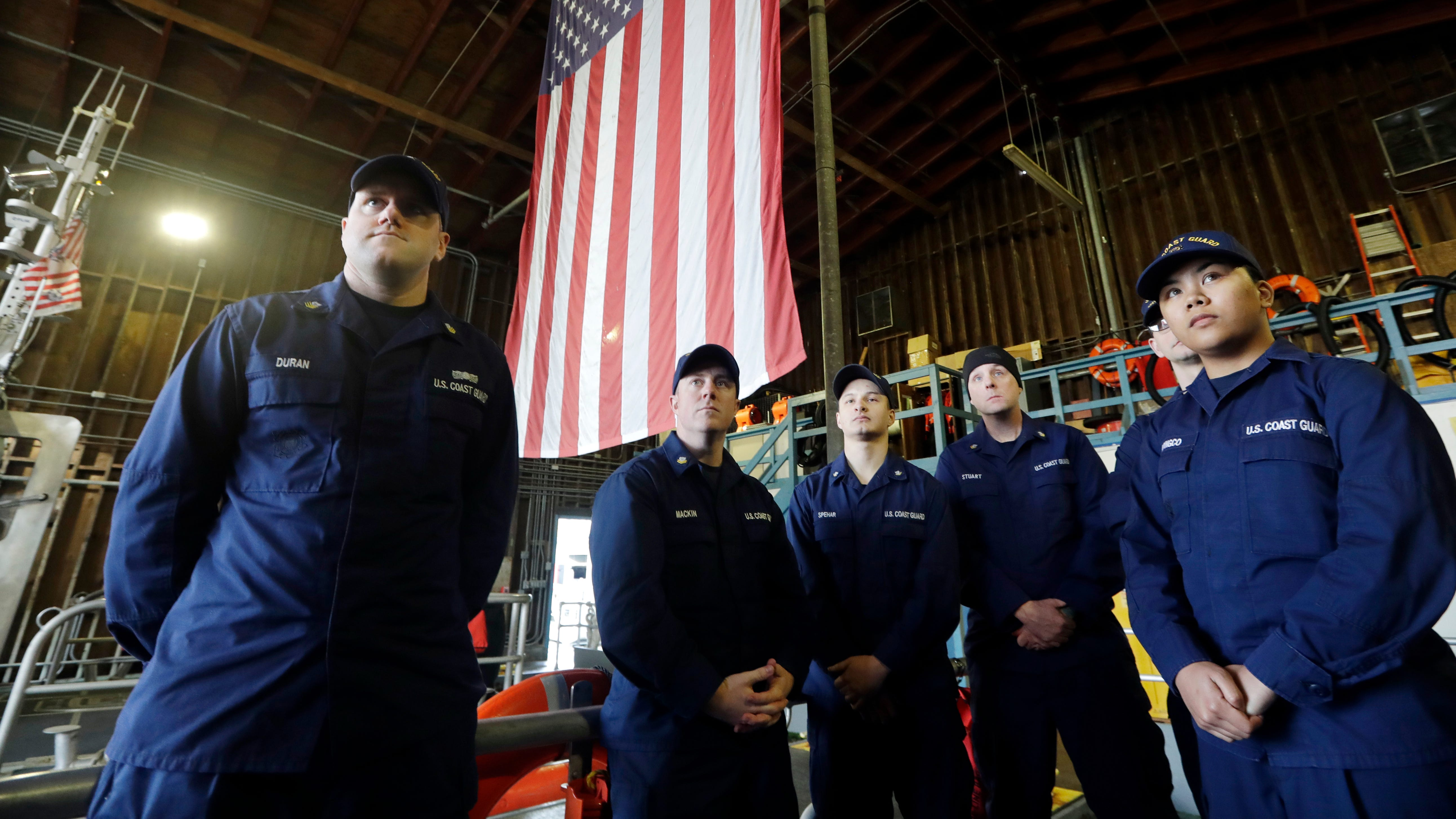 U.S. Coast Guardsmen and women stand on a 45-foot response boat as they listen to their lieutenant during their shift at Sector Puget Sound base in Seattle.