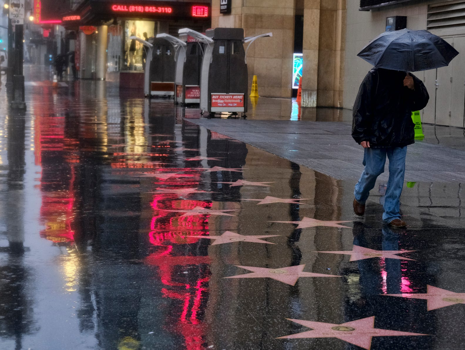 A pedestrians makes his way along a rain soaked Hollywood Blvd. in Los Angeles on Thursday, Jan. 17, 2019. The latest in a series of Pacific Ocean storms pounded California with rain and snow Thursday, prompting officials to put communities on alert for mudslides and flooding and making travel treacherous.