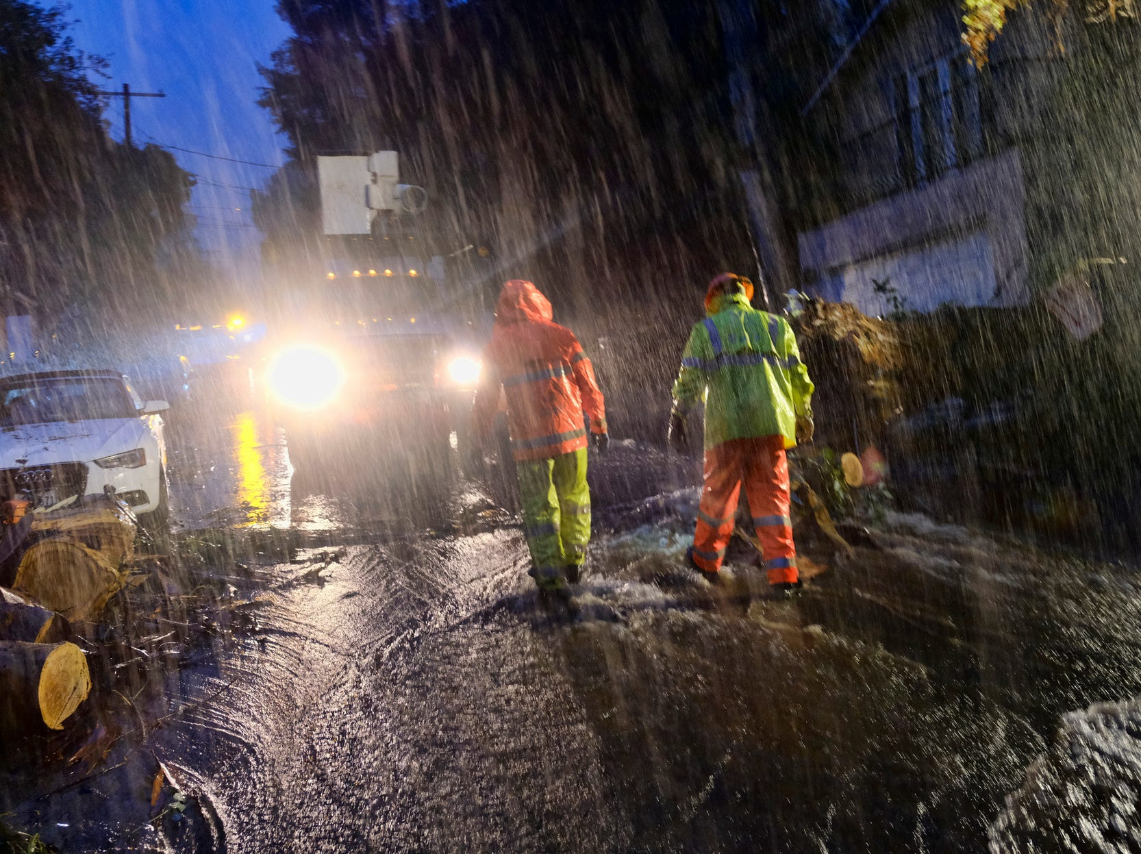 Department of Water and Power employees work in the pouring rain to clear a fallen tree from a road in the Hollywood hills in Los Angeles, Thursday, Jan. 17, 2019.