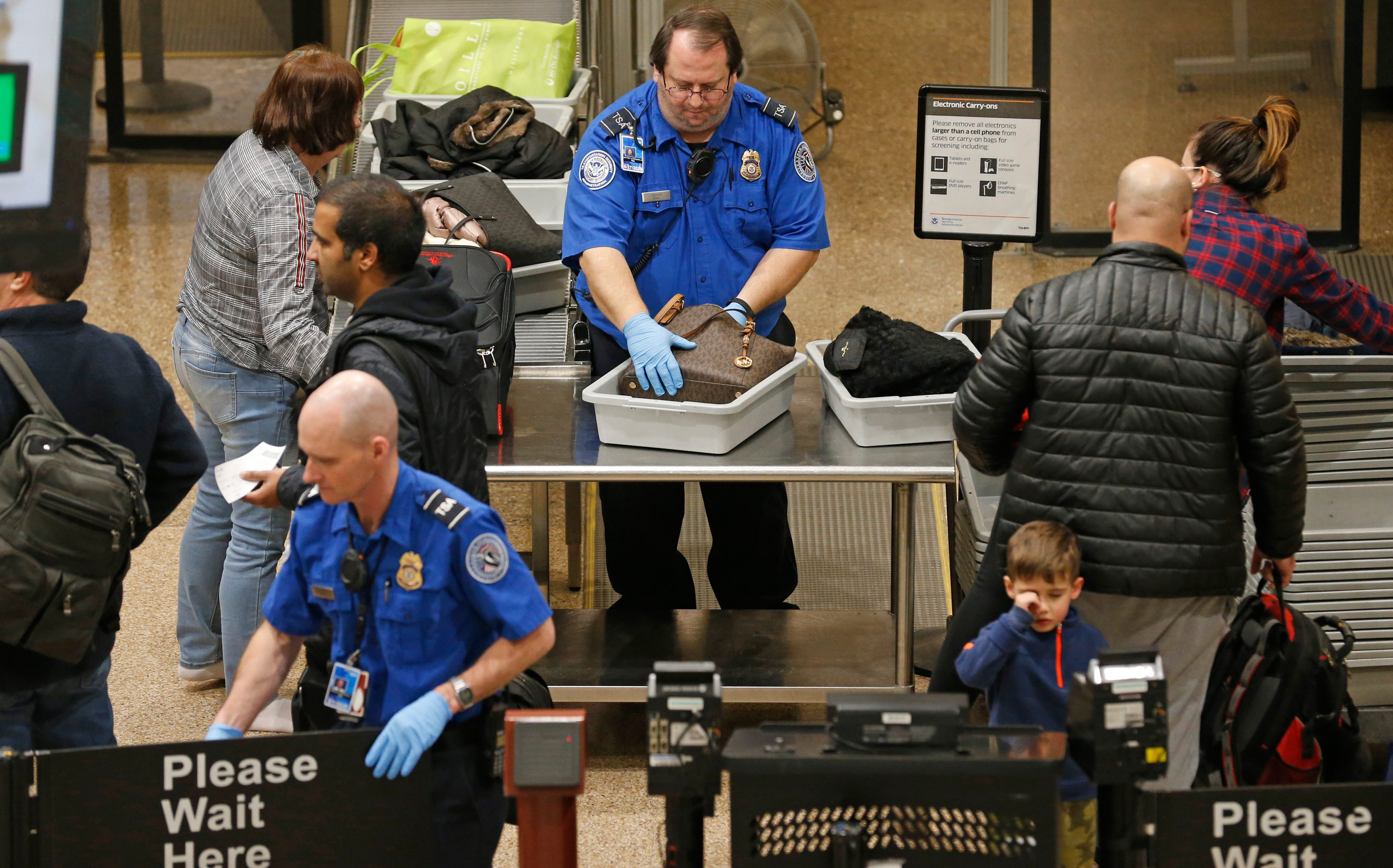 A TSA worker helps passengers at the Salt Lake City International Airport, Wednesday, Jan. 16, 2019, in Salt Lake City. The government shutdown has generated an outpouring of generosity to TSA agents and other federal employees who are working without pay. In Salt Lake City, airport officials treated workers from the TSA, FAA and Customs and Border Protection to a free barbecue lunch as a gesture to keep their spirits up during a difficult time.