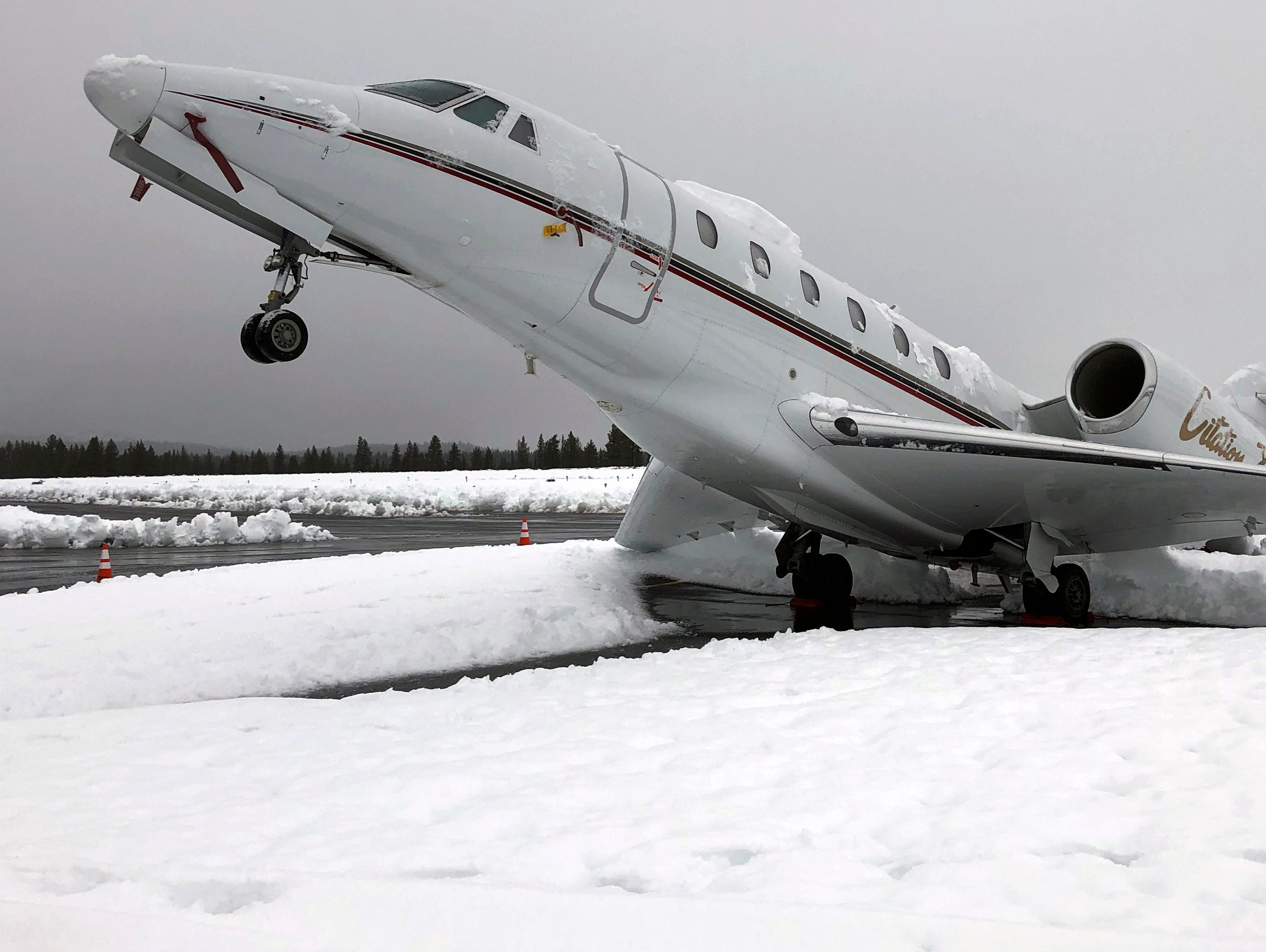 "This Wed. Jan. 16, 2019 photo shows an overnight accumulation of about 20 inches of heavy wet snow dubbed ""Sierra cement"" causing a Cessna Citation X business jet at an outdoor parking spot to do a tail stand at Truckee Tahoe Airport in Truckee, Calif. Airport official Marc Lamb photographed the aircraft before mechanics cleared the snow. No injuries were reported."