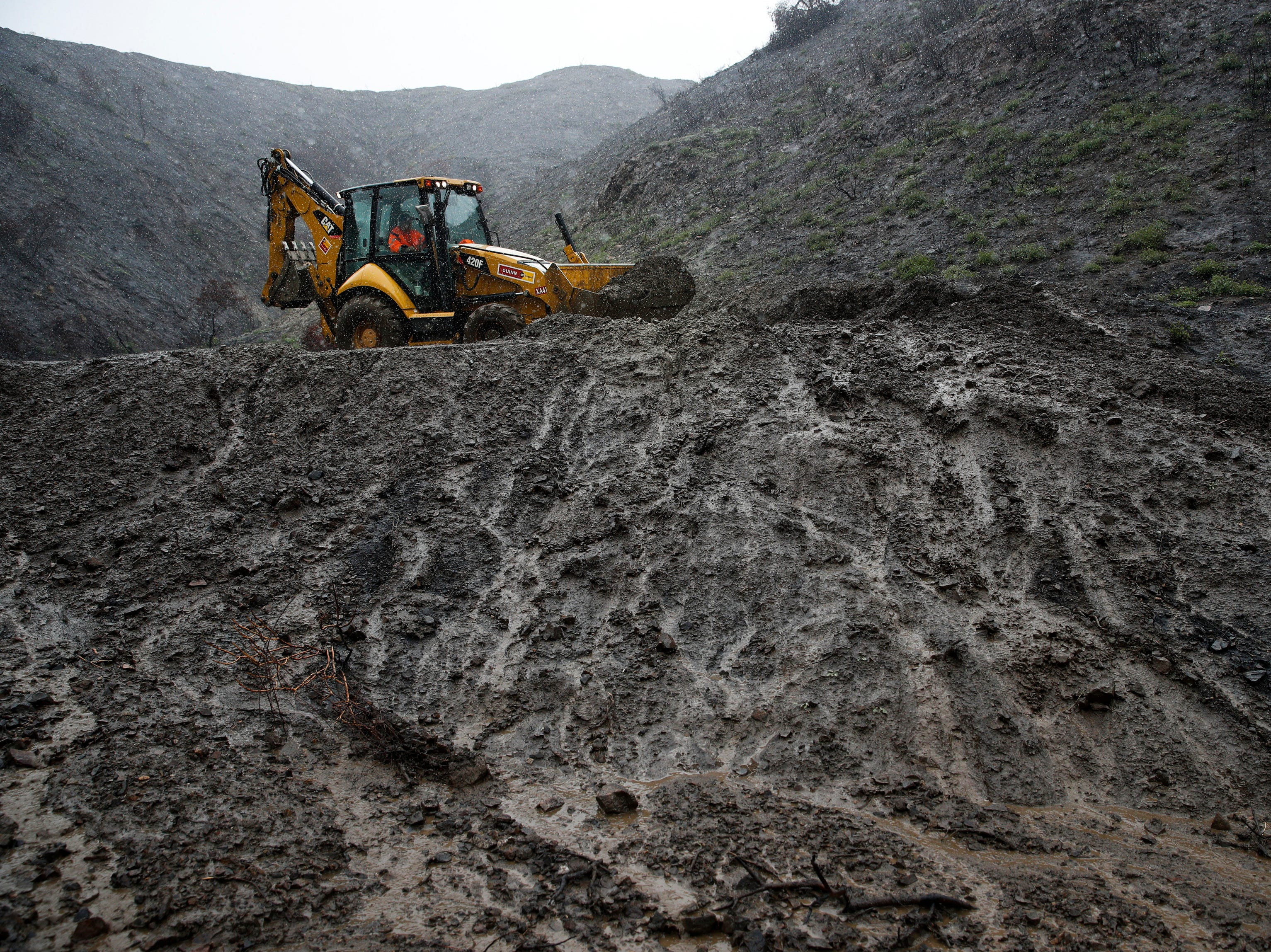 A worker removes a pile of dirt to prevent mudslides in the area burned by last year's Holy Fire Thursday, Jan. 17, 2019, in Lake Elsinore, Calif.