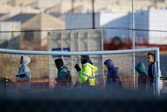 In this Dec. 13, 2018, file photo, teen migrants walk in line inside the Tornillo detention camp in Tornillo, Texas. Government investigators say many more migrant children may have been separated from their parents than the Trump administration has acknowledged.