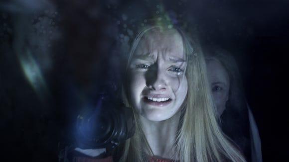 "Becca (Olivia DeJonge) hides from Nana (Deanna Dunagan) in ""The Visit."""