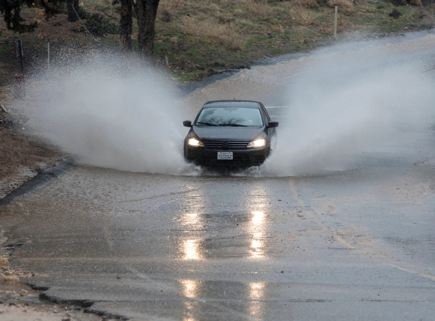 A car hits a deep section of rain run off along Peach Avenue in Hesperia, Calif., Thursday, Jan. 17, 2019.