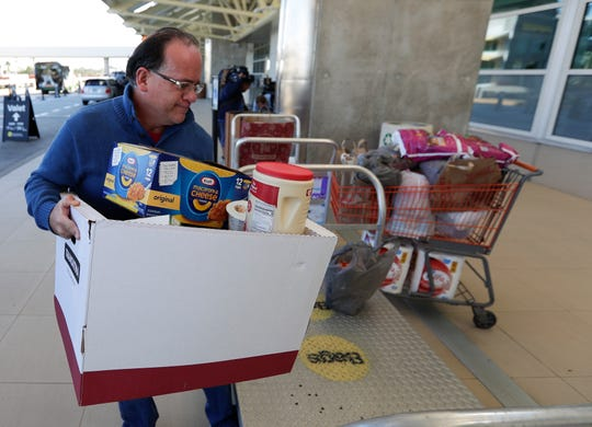 Erwin Guzman drops a donation of food and supplies for TSA workers at Orlando International Airport in Orlando, Fla., on Wednesday. The partial government shutdown is moving through its fourth week.