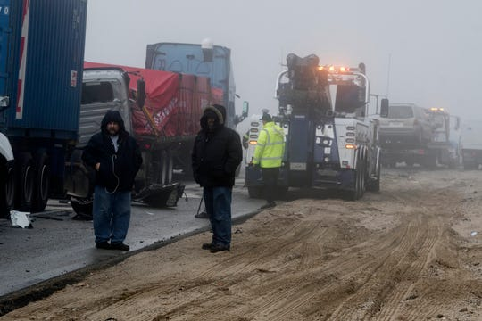 Truck drivers watch damaged semitrailers get removed from the scene of a multi-car collision in the Cajon Pass near Hesperia, Calif., on Wednesday Jan. 16, 2019. (