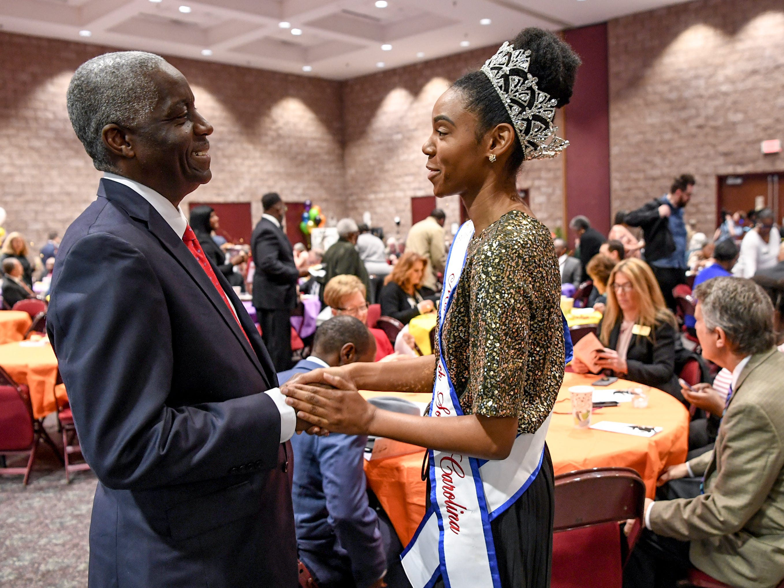 Mayor Terence Roberts, left, and Angel Wheeler, Miss Black South Carolina USA, greet each other during the Mayor's Martin Luther King Jr Breakfast in the Anderson Civic Center Friday, January 18, 2019.