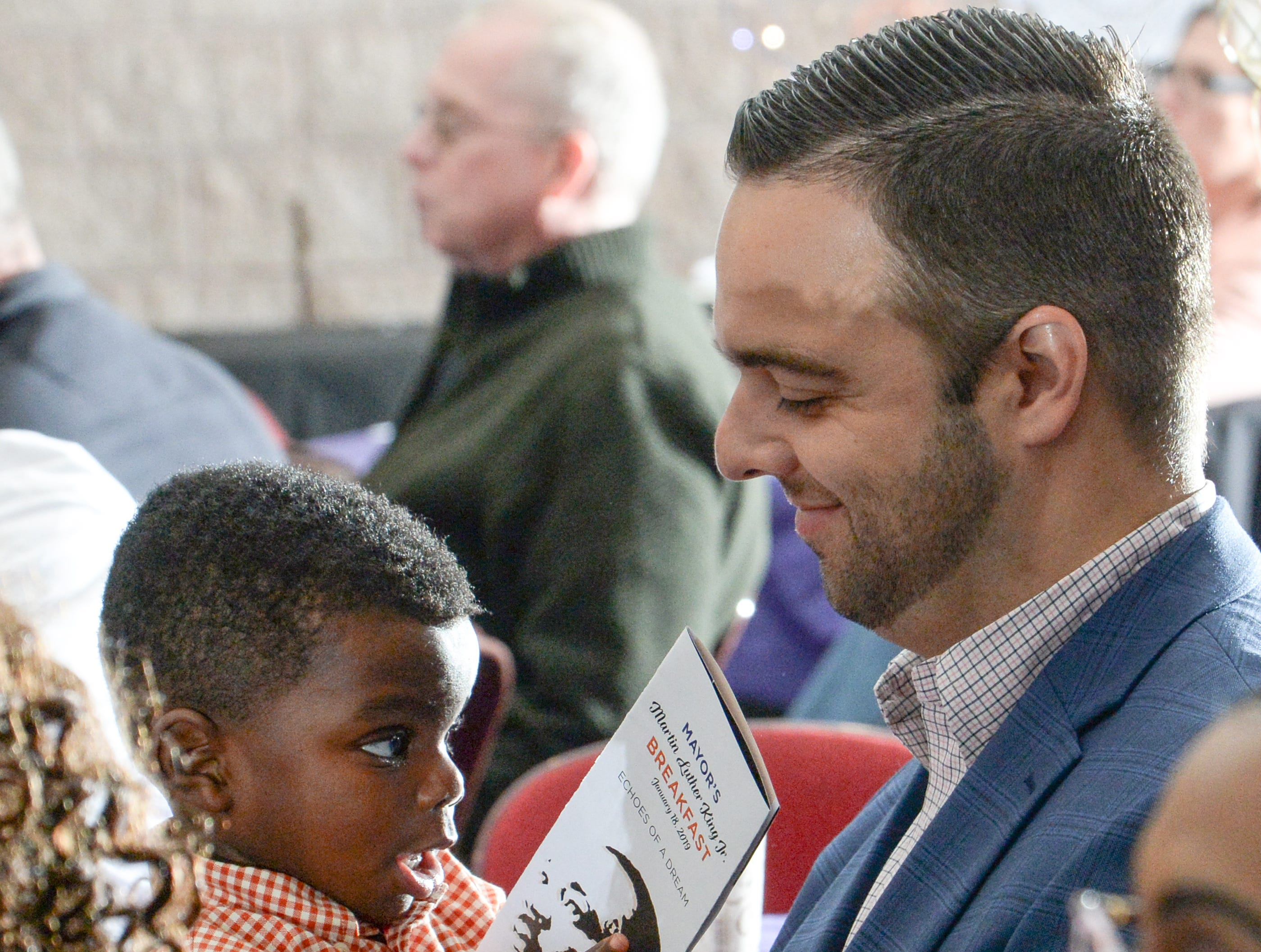 Brazeal Wright, left, holds a program with his father John Wright, Jr., during the Mayor's Martin Luther King Jr Breakfast in the Anderson Civic Center Friday, January 18, 2019.