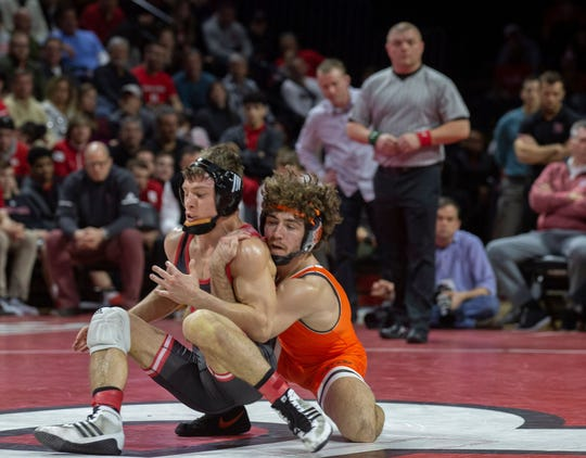 Rutgers' junior 133-pounder Nick Suriano (left) is shown wrestling Oklahoma State's Daton Fix on Jan. 13, was defeated by Iowa's  Austin DeSanto Friday night on a last-second takedown