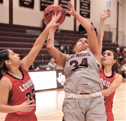 McMurry's Skyler Reyna (34) drives for a shot while Sul Ross State's Lizette Heredia, left, and another player defend. McMurry won the American Southwest Conference game 90-57 on Thursday, Jan. 17, 2019, at Kimbrell Arena.