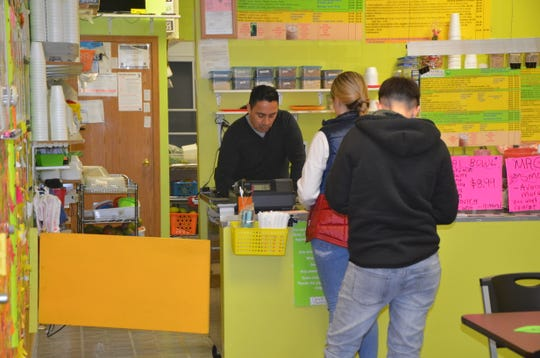 Mango Healthy Fruit and Food owner Alberto Guerrero takes orders at the restaurant's Columbia Avenue location on Jan. 18, 2019.