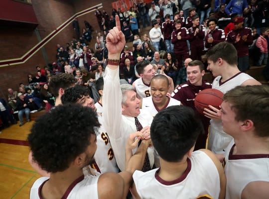 South Kitsap boys basketball coach John Callaghan celebrates with his players following his 300th career win Thursday against Bellarmine Prep.