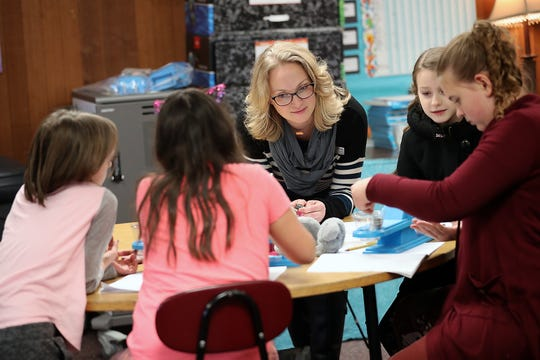 Orchard Heights Elementary School teacher Hillary O'Brien works with students as they investigate the force of attraction between magnets during class in Port Orchard.