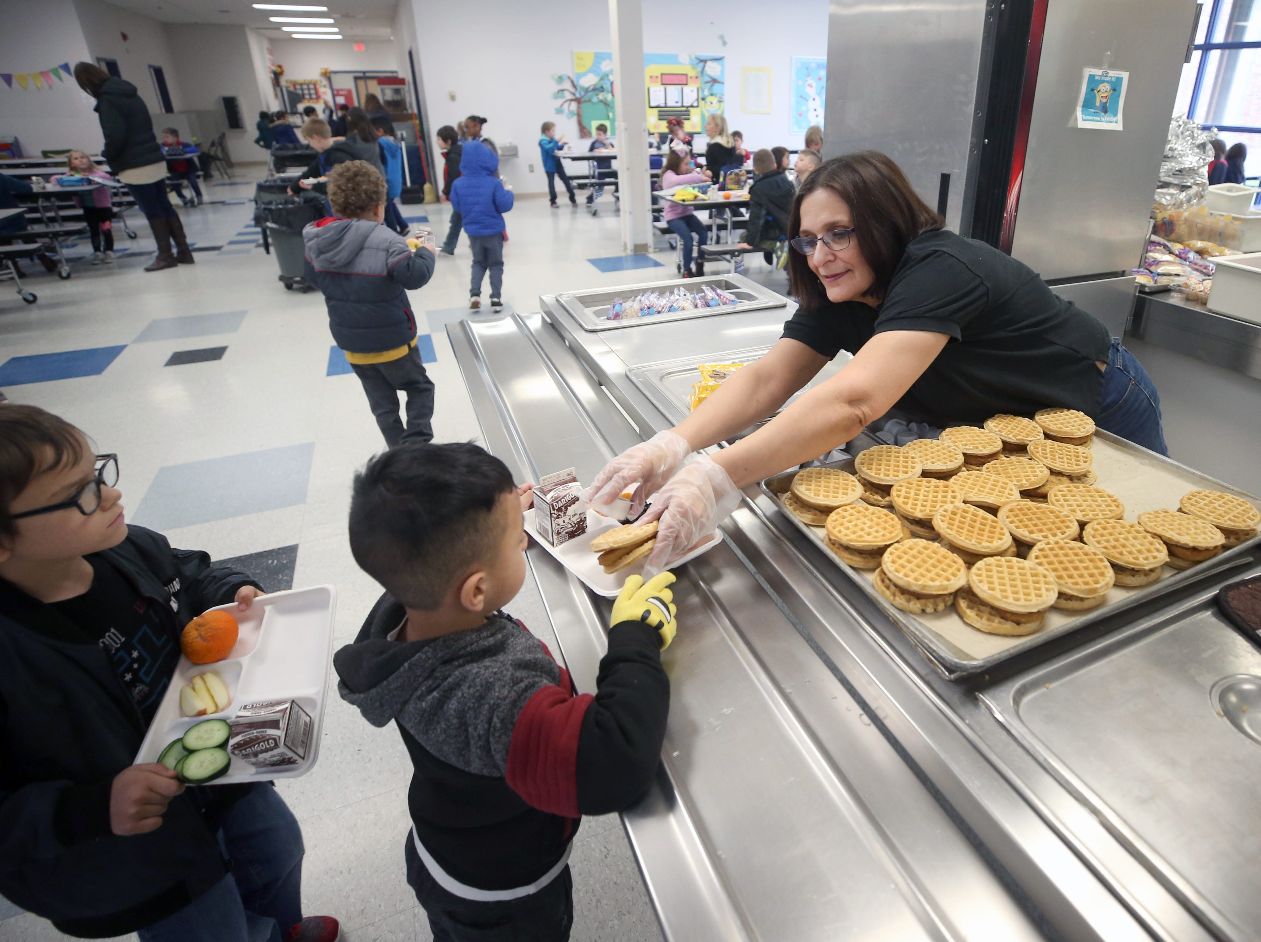 Lunch helper/server Laurie Sheridan puts waffles on a tray to a kindergarten student at East Port Orchard Elementary School on Friday, January, 18, 2019. Local school districts are reminding families affected by the government shutdown that their students may be eligible for free and reduced lunch prices at school.