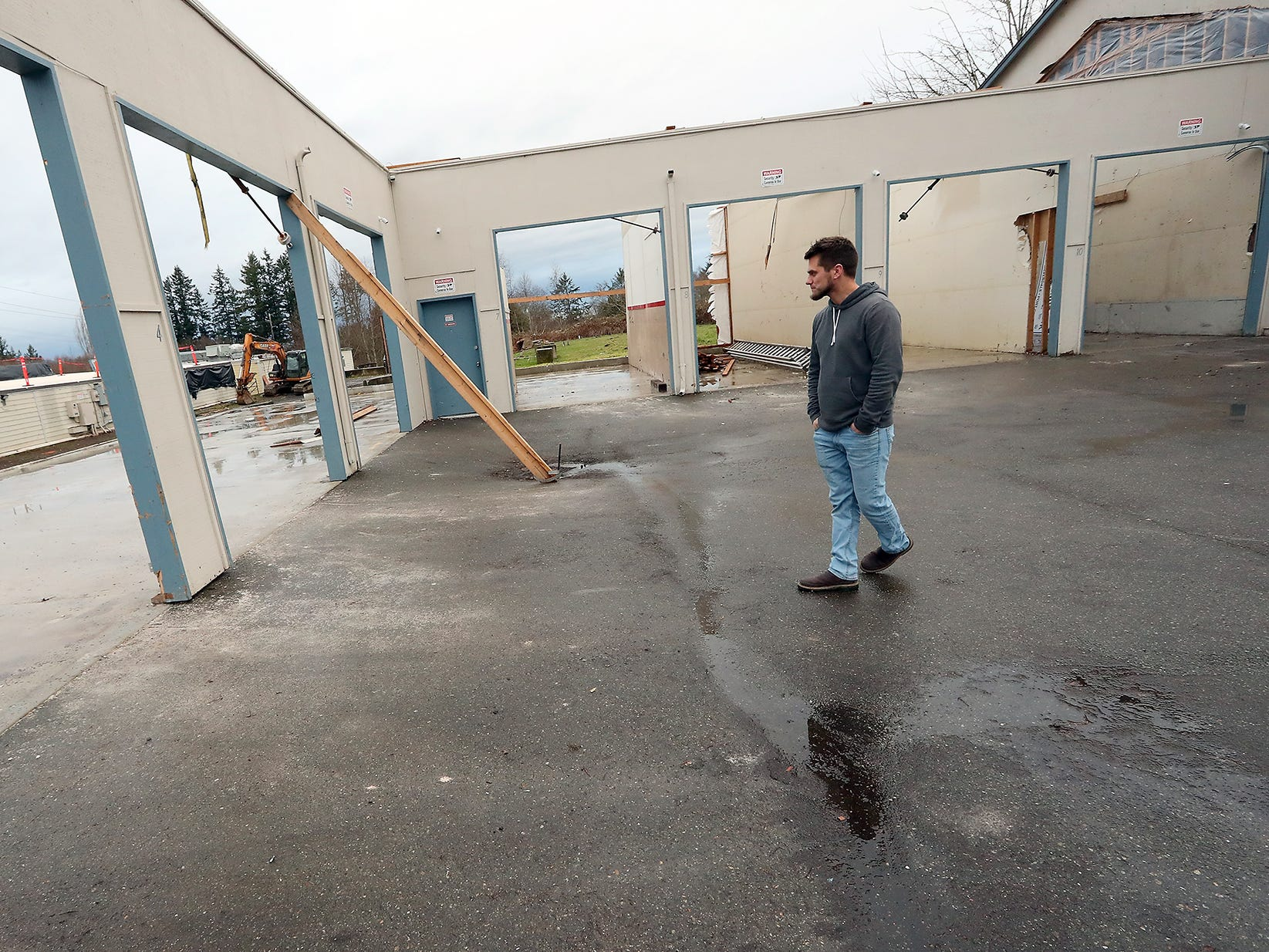 Brady Mueller, of Quality Coating Enterprises, walks through what is left of the storage units at Bethel Square where he and co-owner Austin Siegel ran their business before it was destroyed by the tornado, in Port Orchard on Thursday, January 17, 2019.
