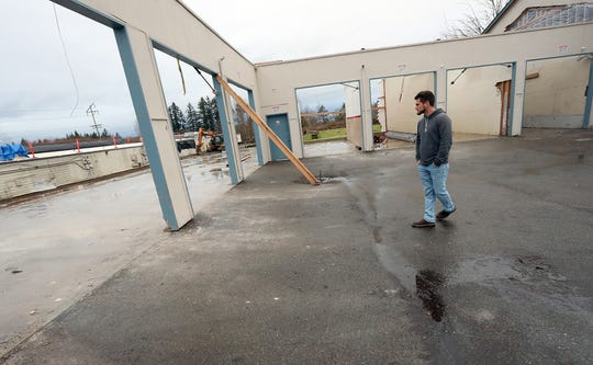 Brady Mueller, of Quality Coating Enterprises, walks through what is left of the storage units at Bethel Square where he and co-owner Austin Siegel ran their business before it was destroyed by the tornado, in Port Orchard.