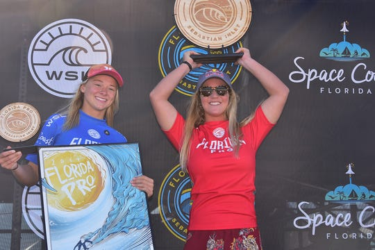 Caroline Marks holds up the trophy after winning her second straight Florida Pro surf contest at Sebastian Inlet, defeating Kirra Pinkerton, left.