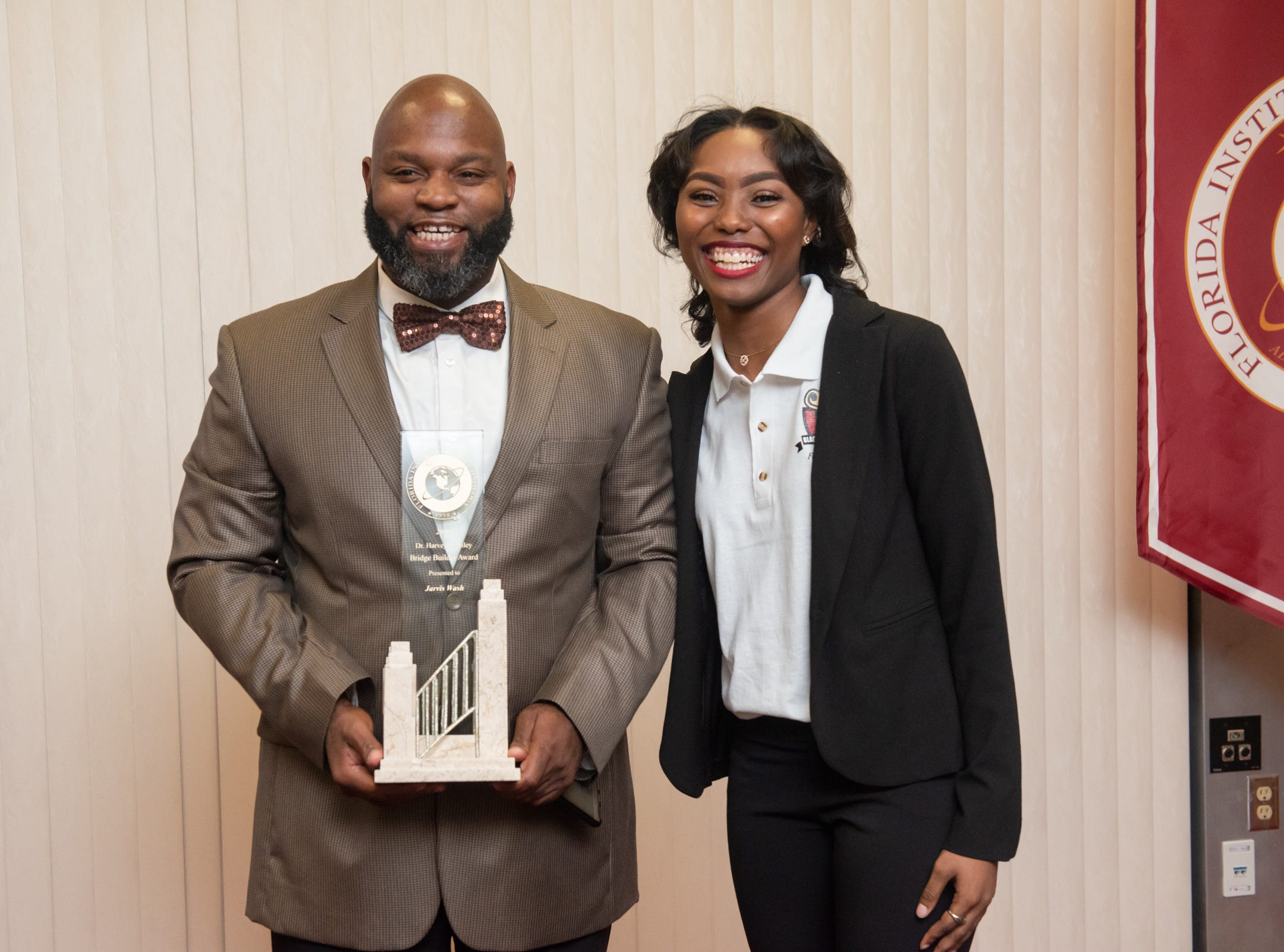 Pastor Jarvis Wash receives the Bridge Builder Award, presented by Black Student Union President Furaha Merritt at the Julius Montgomery Pioneer Award and the Dr. Harvey L. Riley Bridge Builder Award presentation in celebration of Martin Luther King Jr. Day.