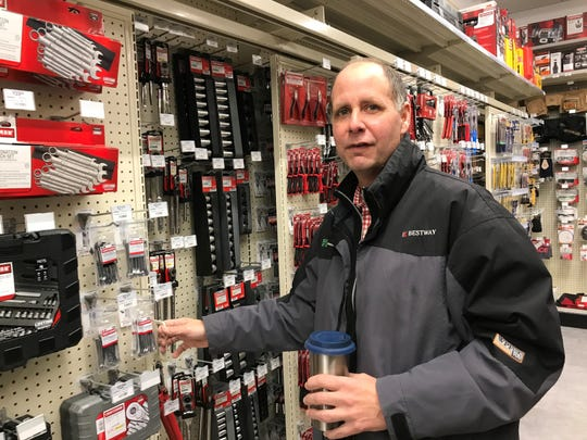 City Hardware owner Gordon Winters demonstrates the store's double sliding racks of tools.
