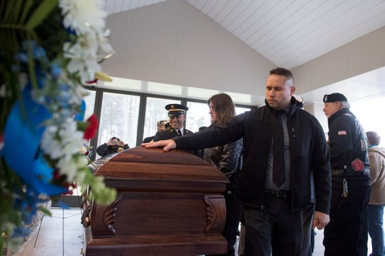Former Army Captain Rogers Ramirez takes a moment with the casket of Vietnam veteran Peter Turnpu as several hundreds gather for a funeral Friday, Jan. 18, 2019 in North Hanover, N.J.