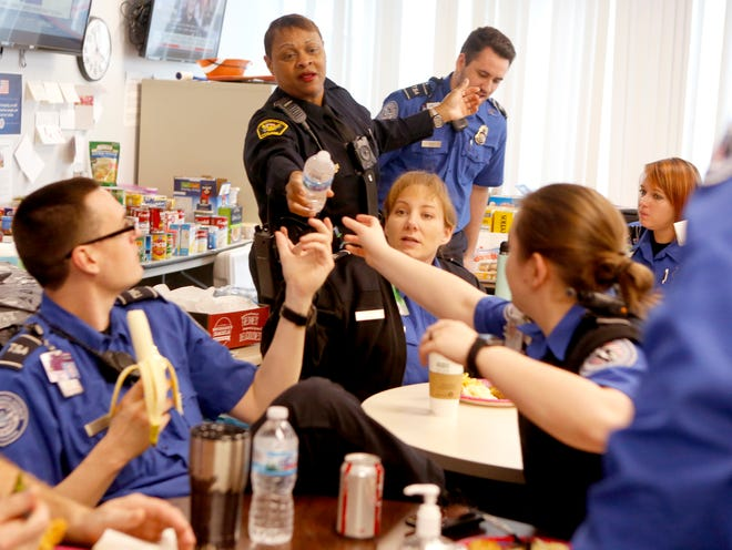 Cincinnati police officer Princess Davis, right, hand out drinks to TSA officers at the Cincinnati/Northern Kentucky International Airport Friday. Cincinnati police brought a meal to the TSA officers to support them while they work unpaid during the partial government shutdown.