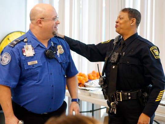 Cincinnati police officer Princess Davis, right, jokes with a TSA officer at the Cincinnati/Northern Kentucky International Airport Friday. Cincinnati police brought a meal to the TSA officers to support them while they work unpaid during the partial government shutdown.
