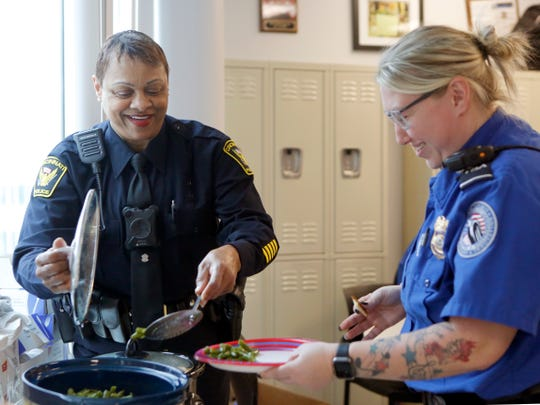Cincinnati police officer Princess Davis, right, serves green beans to a TSA officer at the Cincinnati/Northern Kentucky International Airport Friday. Cincinnati police brought a meal to the TSA officers to support them while they work unpaid during the partial government shutdown.