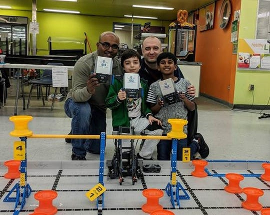 TEECS' E-Smart team Gagan Voonna and Levent Yildiz came in first place, picutred with their fathers. The coach, not pictured is Samuel Obeng.