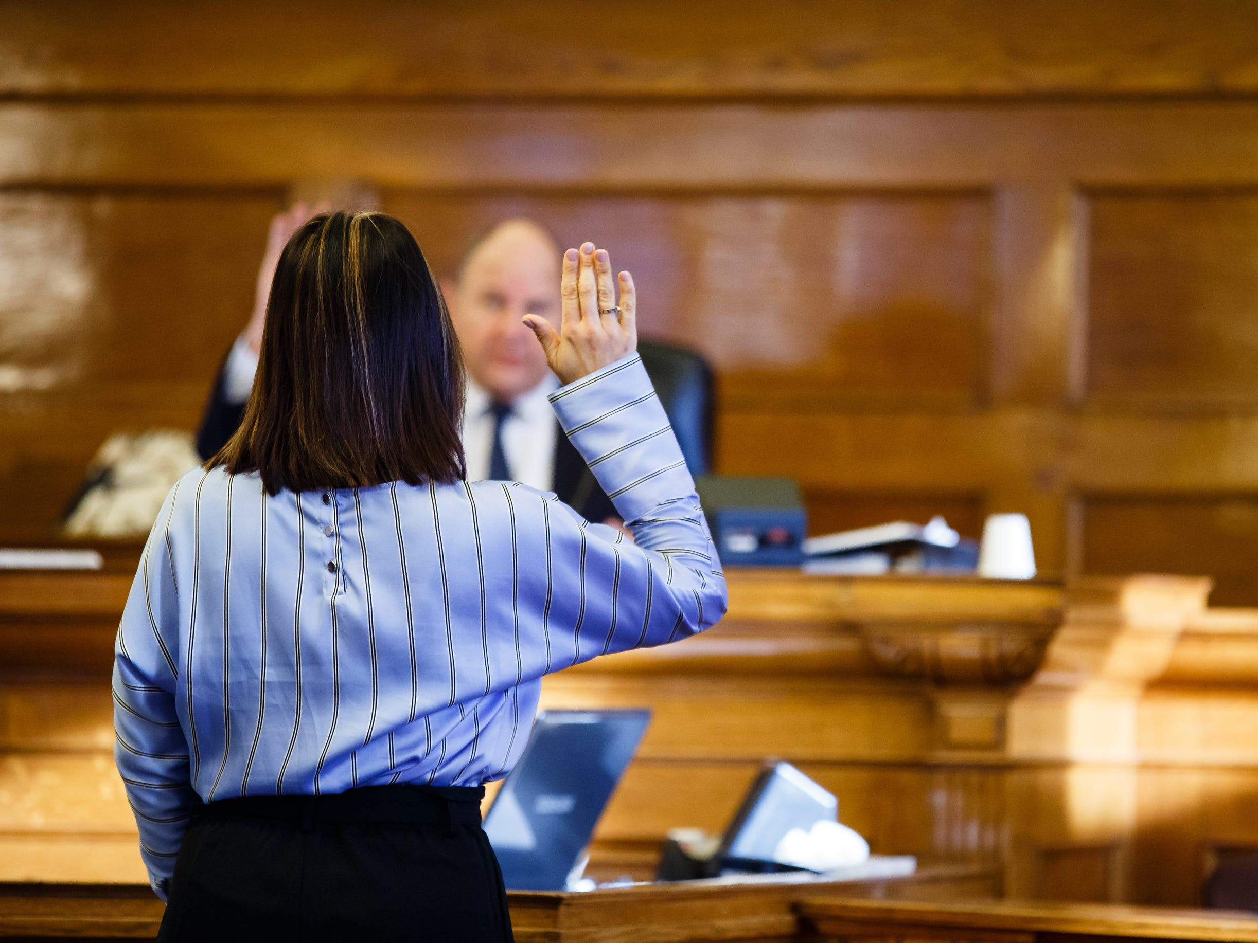 Gina Battani raises her right hand as she is sworn in before giving testimony against her ex-husband Troy Griffin at the Dallas County Courthouse on Tuesday, Oct. 23, 2018, in Adel. The Dallas County jury found Griffin not guilty of raping Battani.