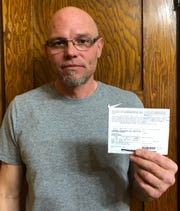 Frank Swanger of Sioux City, who is a felon, successfully fought a felony election misconduct charge after he voted in Iowa's November 2016 election. But it cost him more than $10,000 and three weeks in jail. He said election workers encouraged him to cast a ballot. He is holding his voter ID.