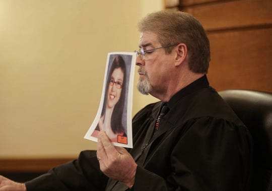 Judge Terry Rickers holds up a photo of Sabrina Ray prior to handing down a sentence of prison time for Marc and Misty Ray in the death of their adopted daughter, Sabrina Ray, on Friday, Jan. 18, 2019, at the Dallas County Courthouse in Adel.