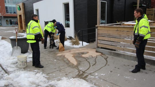 Using kitty litter, Des Moines firefighters work to remove blood from the sidewalk after an overnight shooting in front of the Lime Lounge in Des Moines' East Village. on Friday Jan. 18, 2019