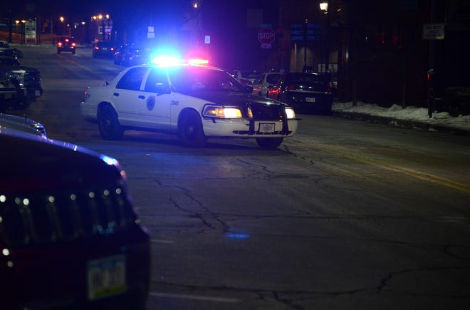 A Des Moines police squad car blocks East Fifth Street on Friday, Jan. 18, 2019, as officers investigate a shooting in the nearby 400 block of East Grand Ave in the city'sHistoric East Village neighborhood.