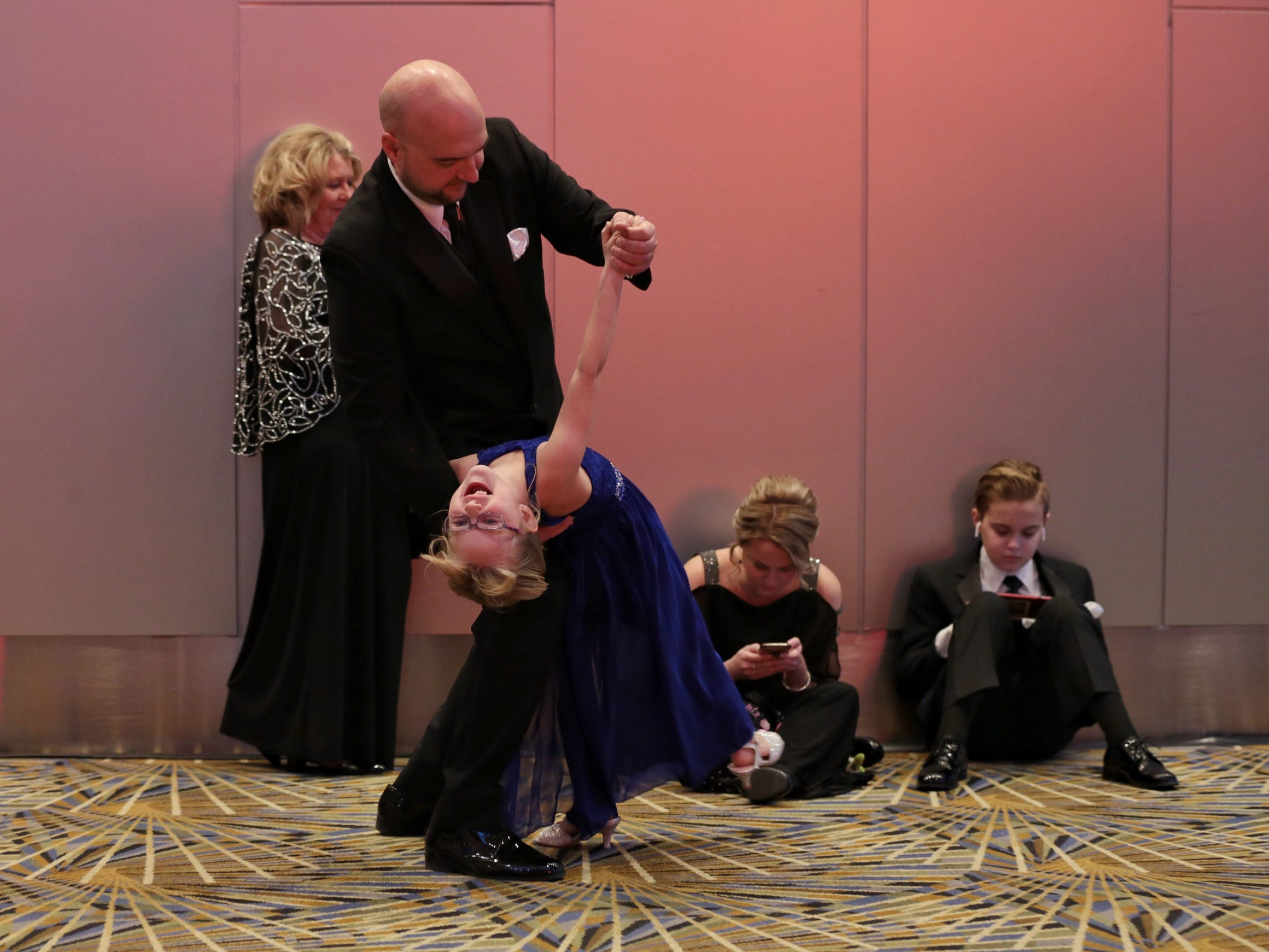 Bill Laskowski of Brownstown, twirls his daughter Lily Laskowski while waiting for the ribbon cutting during the 2019 North American International Auto Show Charity Preview at Cobo Center in Detroit on Friday, January 18, 2019.