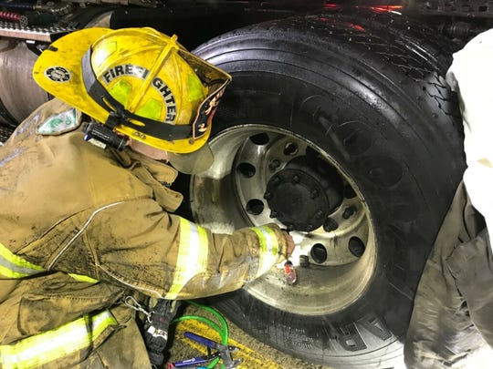 Livonia firefighter Adam Pryor works to free the mechanic trapped between two semi tires in Plymouth on Jan. 17, 2019. The Livonia Fire Department assisted the Plymouth Twp. Fire Department in the rescue.