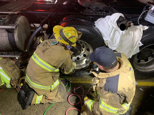 Firefighters working to extricate a man trapped between two semi tires in Plymouth on Jan. 17, 2019. The Livonia Fire Department assisted the Plymouth Twp. Fire Department in the rescue.