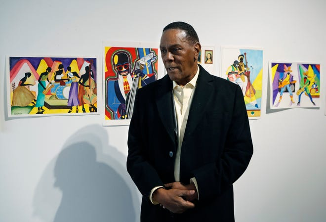 In this Thursday, Jan. 17, 2019 photo, Richard Phillips stands next to some of his artwork during an interview at the Community Art Gallery in Ferndale.