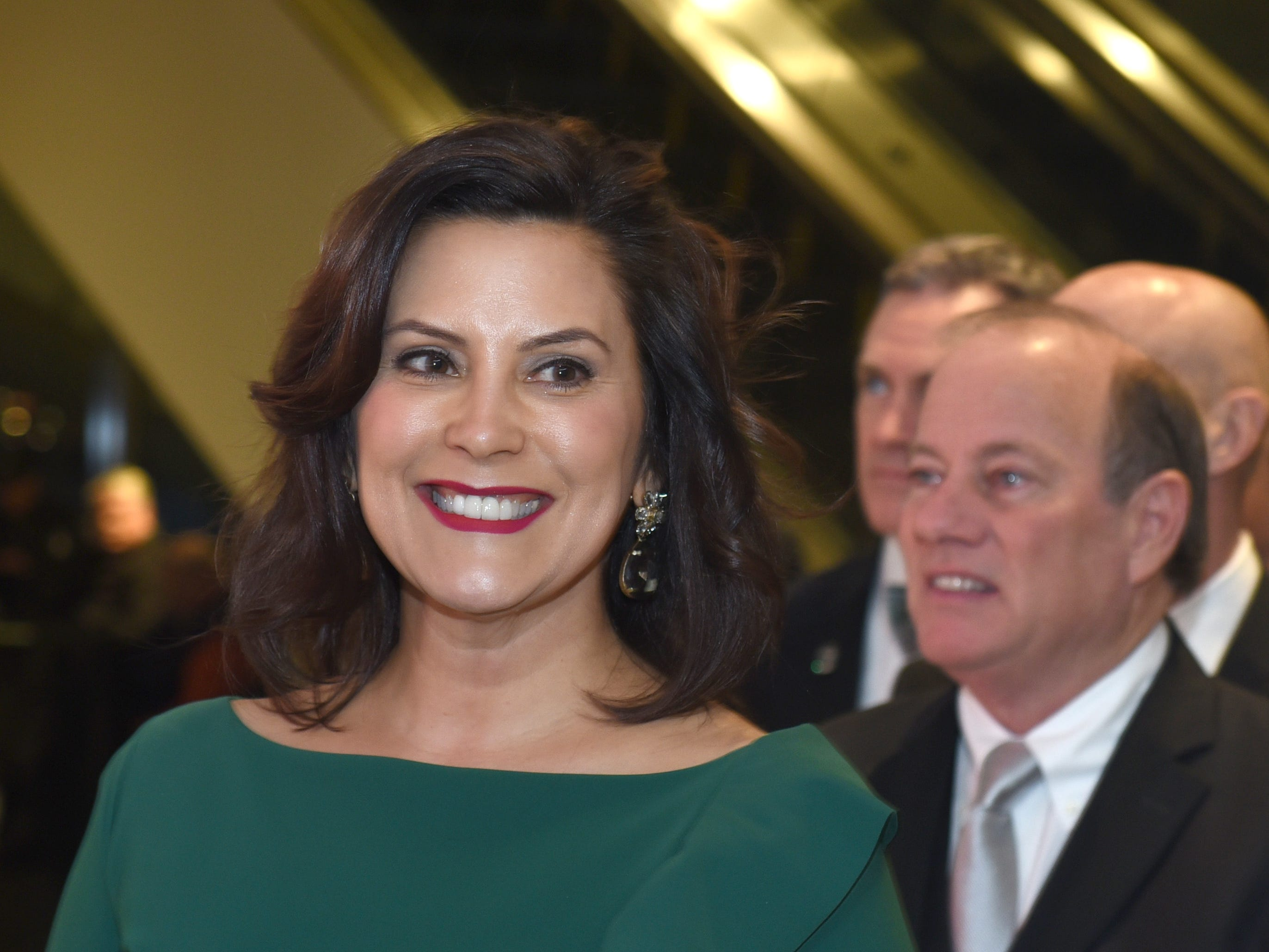 Gov. Gretchen Whitmer smiles as she enters the atrium stage with Detroit Mayor Mike Duggan behind her.