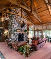 The home features a wood-burning fireplace, a covered dock, a six-stall horse barn and a guest house.