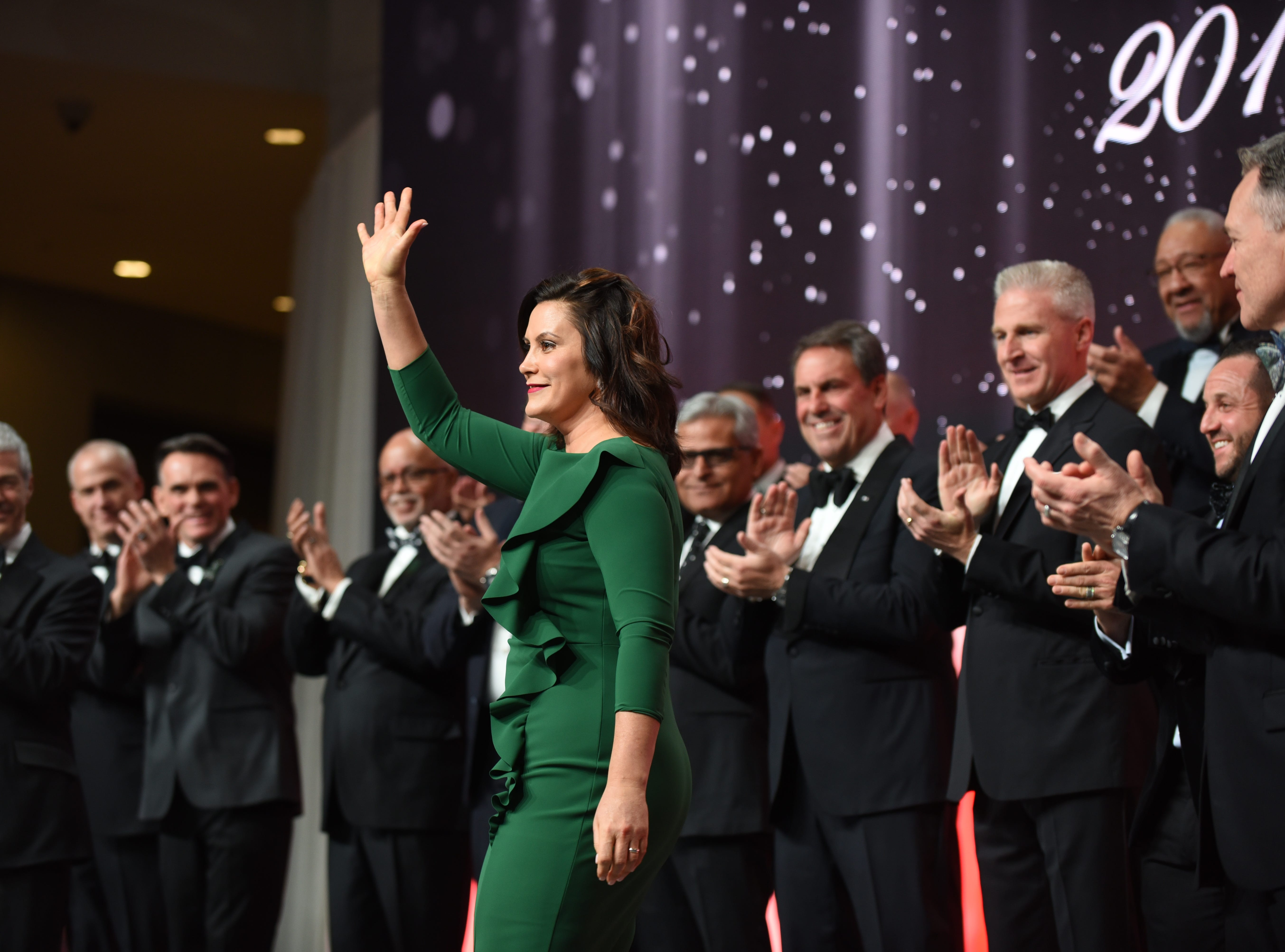 Gov. Gretchen Whitmer waves as she is introduced during the ribbon-cutting ceremony at the 2019 Auto Show Charity Preview.