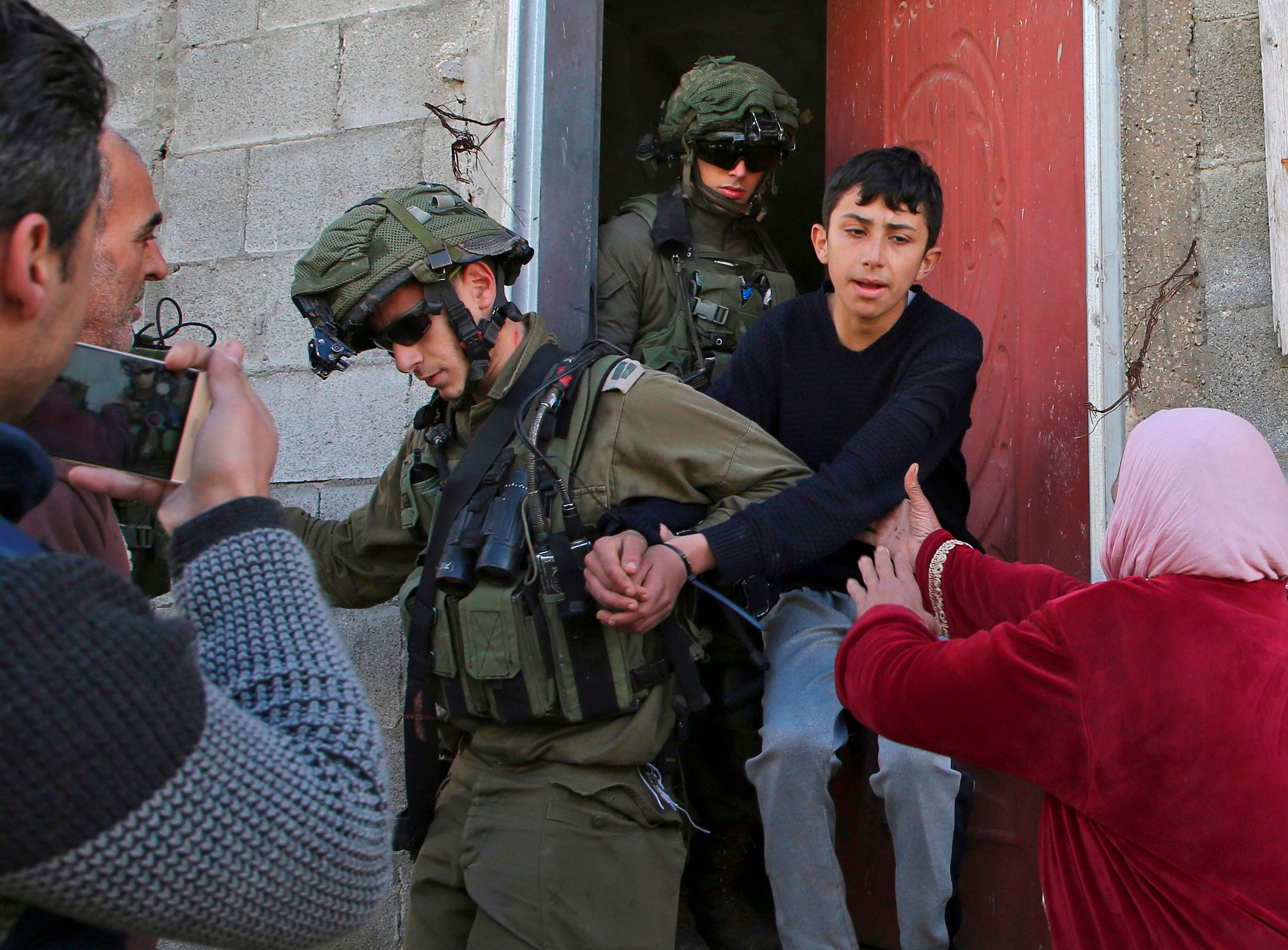 Israeli soldiers a Palestinian youth into custody as a Palestinian woman protests following a demonstration against the expropriation of Palestinian lands by Israel in the village of Kfar Qaddum, near Nablus in the occupied West Bank, on Jan. 18, 2019.