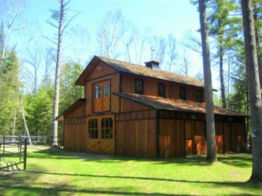This white cedar log mansion situated on 60-acres of woods on the edge of  Lake Charlevoix lists for $7 million and features six bedroom and five bathrooms. The 4,420-square-foot house is located on Mountain Road in East Jordan, which is about 260 miles north and west of Detroit and 15 miles south of Charlevoix. The house has a private, gated drive complete with a covered bridge. It includes more than 3,000 feet of sandy beach on Lake Charlevoix and comes with a guest house and horse barn.